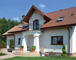 Zwarta bryła domu ma dwuspadowy dach o nachyleniu 40°, pod którym ułożono wełnę mineralną (24 cm), a na zewnątrz – czerwoną blachodachówkę. Ściany budynku są dekoracyjne – ozdobione dwoma wykuszami i balkonami, efektownym gankiem i tarasem. Wykończono je tynkiem mineralnym i farbą silikonową