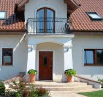 Front domu, zwrócony na południowy zachód, dekoruje ganek i zadaszony balkon. Zabezpieczono go kutą stalową balustradą. Podpierają go murowane słupy i podcień z łukiem, osłaniające drzwi wejściowe. Łukowatą formę mają też schody, murki przy ganku i zwieńczenie okna na balkonie